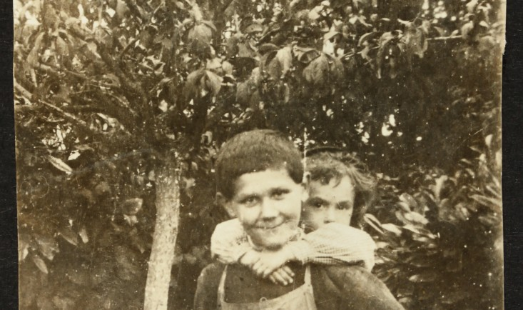 Photograph of a young boy wearing apron, standing beside fruit tree with child on his back, c.1910. National Trust, Lanhydrock, Cornwall © National Trust / Anne Chapman & Dave Presswell