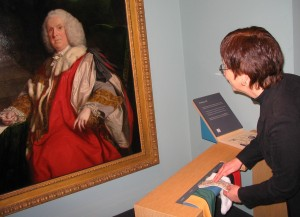 A visitor to Beningbrough Hall handling and identifying samples of the fabrics depicted in the adjacent portrait © National Portrait Gallery, London