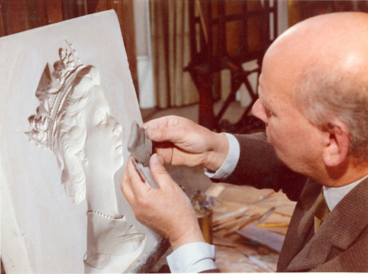 Arnold Machin (1911-1999) taking a clay impression from the mould © Royal Mail Group Ltd 2012 courtesy of The British Postal Museum & Archive