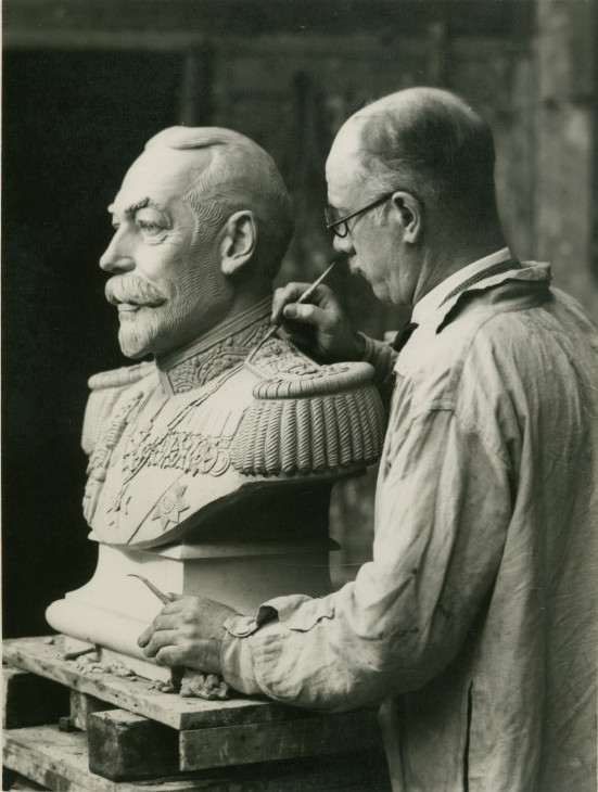Photograph of Herbert Tyson-Smith working closely on a sculpture of a bust, possibly George V ©National Trust Images/Edward Chambré Hardman Collection
