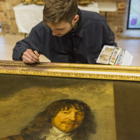 National Trust conservator Mark Searle touching up an 18th-century frame with watercolours in the new conservation studio at Knole, Kent © National Trust Images/James Dobson