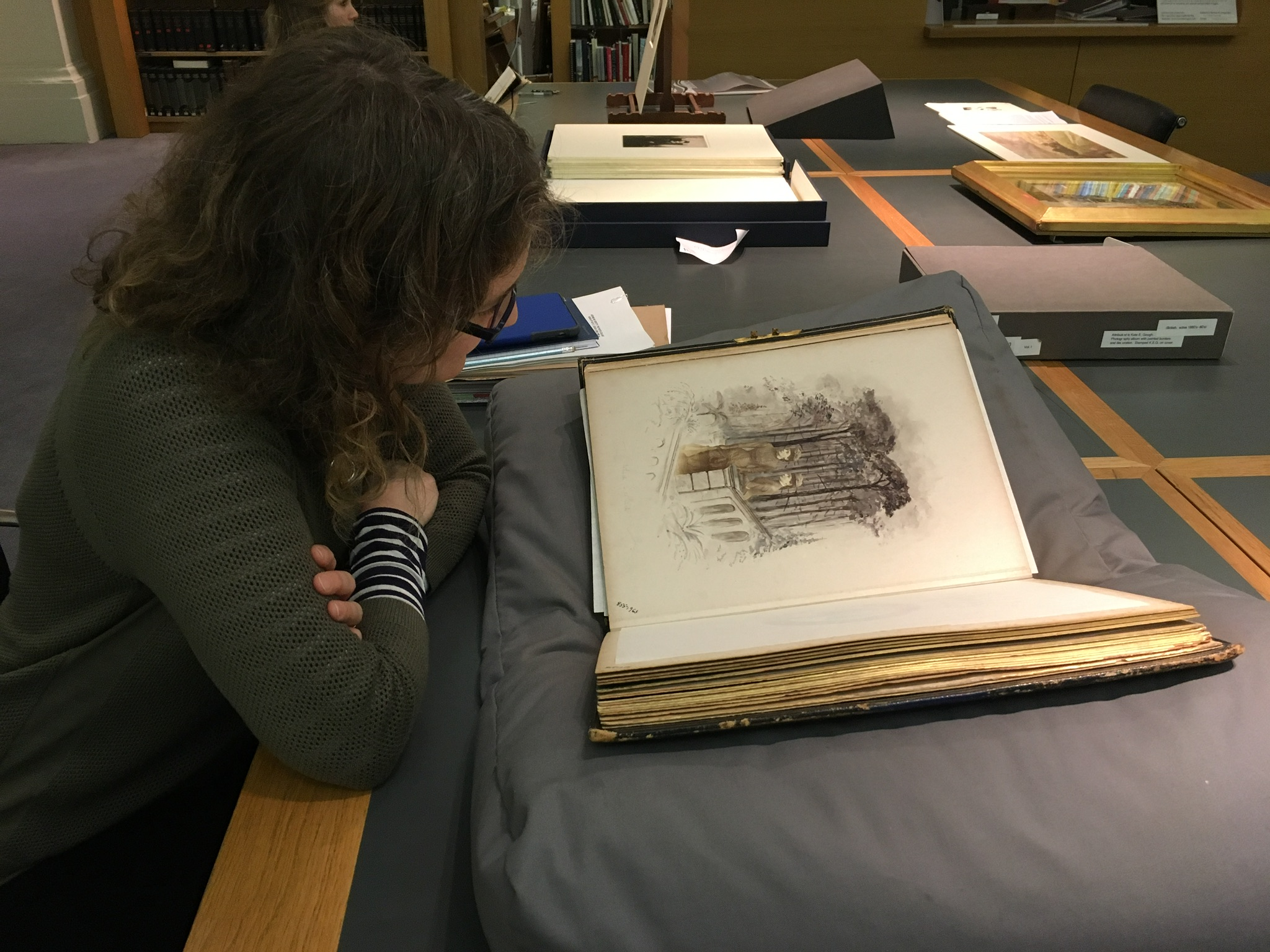 Kate Noble with Kate Gough's photo-collage album in the V&A Museum